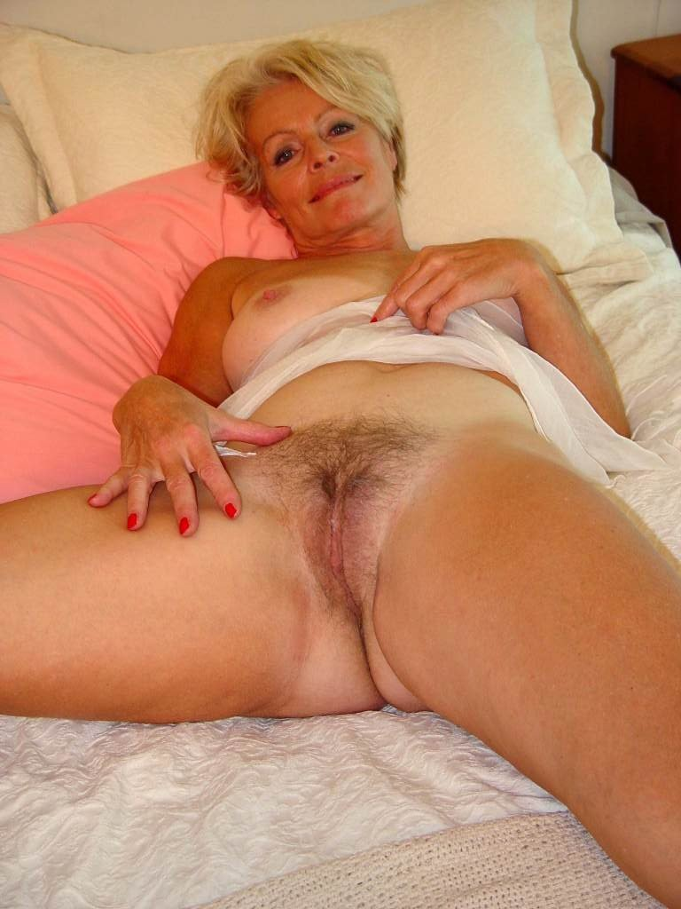 Mature justine posing naked on the bed